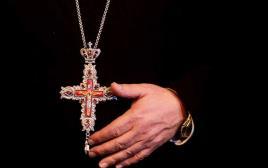 נוצרי אוחז בצלב שלו