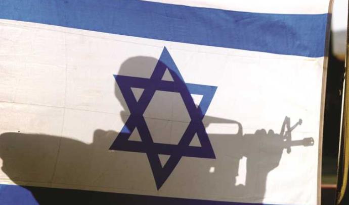 """חייל צה""""ל ליד דגל ישראל"""