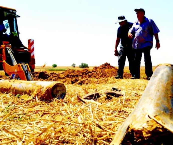 חקלאים בעוטף עזה ליד רקטה. ארכיון