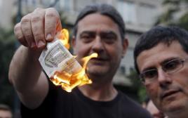 אדם שורף יורו במחאה ביוון