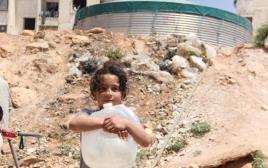 ילדה סורית מחכה למים בחאלב הנצורה