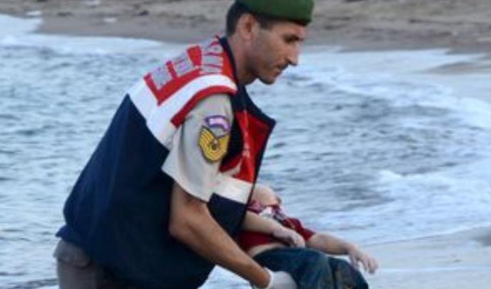 הקצין הטורקי נושא את הפעוט הסורי
