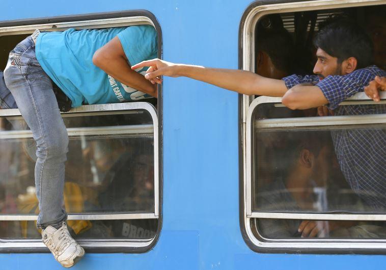 גם דרך החלון. מהגרים עולים לרכבת בקרואטיה