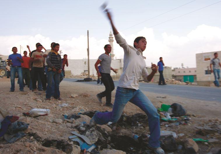 """""""הילדים האלה ראו את מה שאירע בדומא עם משפחת דוואבשה"""". נערים פלסטינים מיידים אבנים. צילום: רויטרס"""