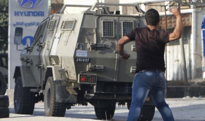 """צעירים פלסטינים משליכים אבנים במהלך עימותים עם צה""""ל"""