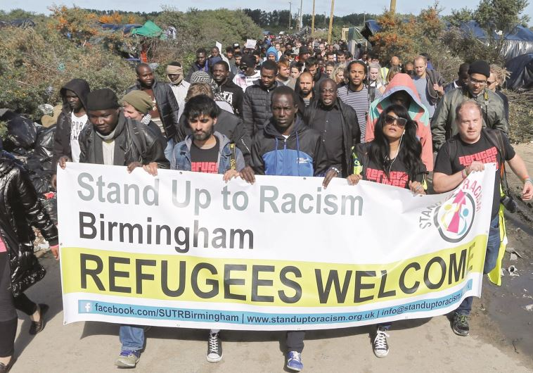 פליטים ונציגי ארגוני סיוע בהפגנה. צילום: רויטרס