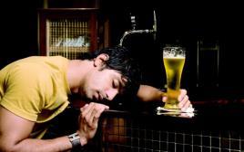 גבר שיכור עם כוס בירה בפאב