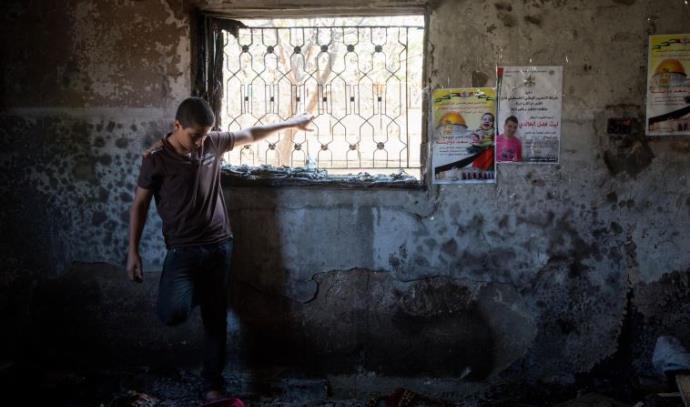 נער פלסטיני מביט על הנזק בבית שהוצת בדומא