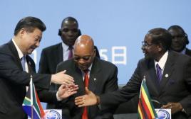 נשיא זיבממווה רוברט מוגבה לוחץ את ידו של נשיא סין שי ג'ינפינג