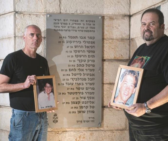 רון קרמן (משמאל) ויוסי צור עם תמונות ילדיהם באנדרטה לזכר נרצחי הפיגוע בקו 37