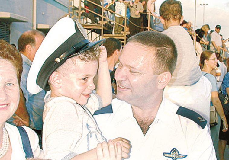 1998. אמיר מגיע עם אח״י דולפין ונושא בזרועותיו את הבן מתן. צילום: רוני שיצר