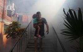 אדם מאל סלבדור ובנו יוצא מביתו לאחר שרשויות הבריאות ריססו אותו נגד הנגיף