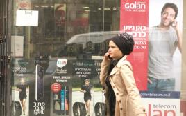 אישה חרדית על רקע כרזות פרסומת