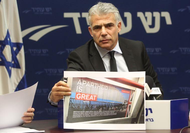 יאיר לפיד עם אחת הכרזות של ה-BDS