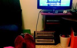 אשה יושבת בסלון מול הטלוויזיה