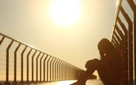 אישה לבדה על חוף הים