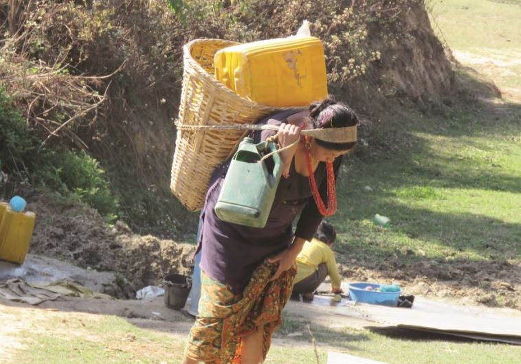 כל ג'ריקן ממולא ב־20 ליטר מים. אישה חוזרת מהבאר שבעמק מתחת לכפר. צילום: סטפני רינת סמית'