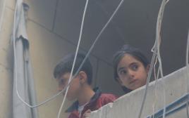 ילדים מביטים על ההריסות בעיר חלב