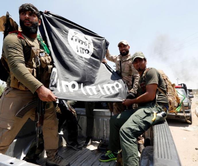 לוחמים שיעים מציגים דגל דאעש שנתפס בלחימה בפלוג'ה