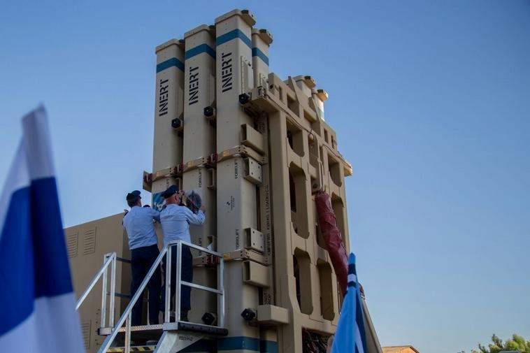 מפקד הגדוד מדביק את סמל החיל והגדוד על מערכת הטילים שרביט קסמים