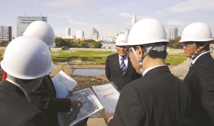 מהנדסים יפנים על הרקע השטח בו יקום האצטדיון האולימפי