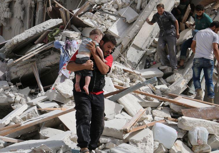 חילוץ ילדים מבין ההריסות בחאלב. צילום: רויטרס
