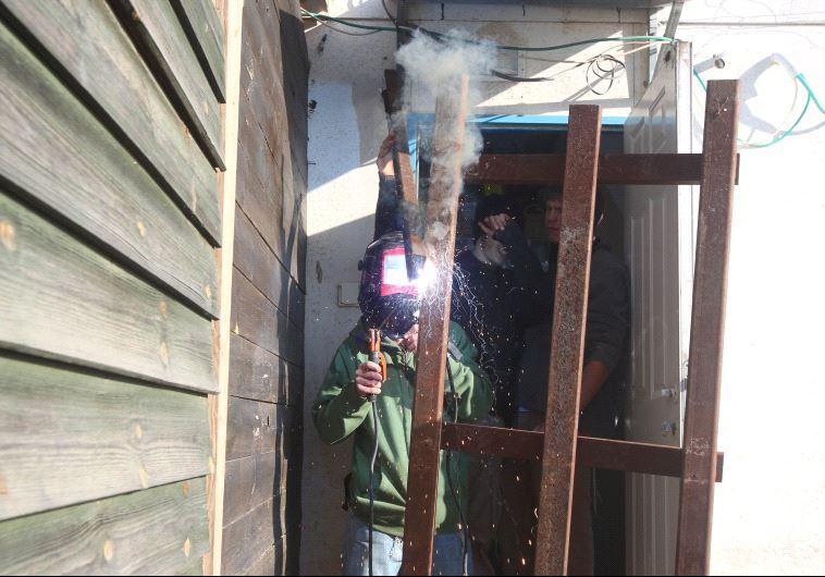 תושב עמונה מרתך חלון על מנת להקשות על פינוי. צילום: מרק ישראל סלם