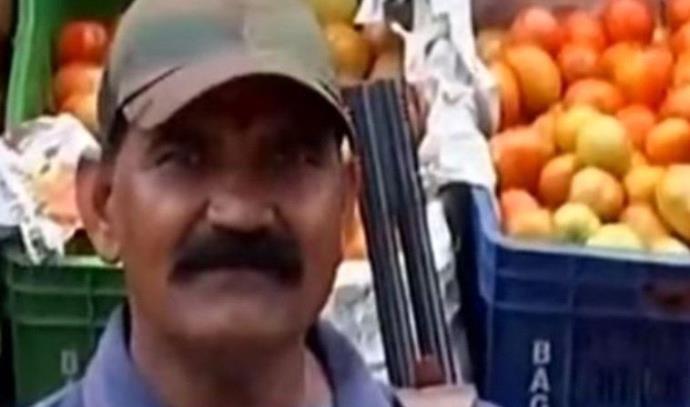 שומר חמוש שומר על משלוח עגבניות בשוק בהודו